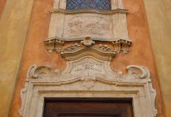 """Particolare della sommità del portale dell'oratorio del Canossa che commemora il terremoto """"A solo excitavit pietas ann. MDCCLIX"""" (dal suolo ha fatto sorgere la pietà, 1759)."""